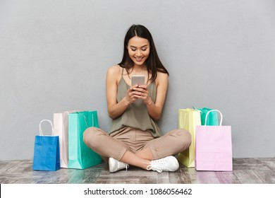 Portrait of a smiling asian woman sitting on a floor with lots of gift boxes and holding mobile phone over gray background