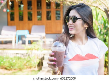 A portrait of smiling Asian woman with sunglasses drinking iced coffee at the outdoor garden coffee shop