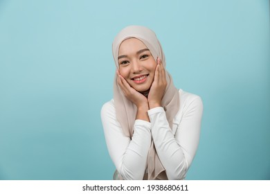 Portrait of smiling Asian young Muslim woman in hijab head scarf standing against blue colour background