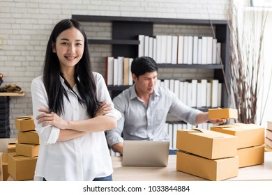 Portrait of smiling asian young woman with cardboard boxes standing in house office,startup Online Marketing concept