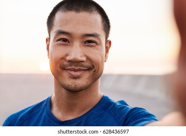 Portrait of a smiling athletic young Asian man in sportswear taking a selfie while out for a solo early morning run