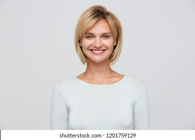 Portrait of a smiling attractive blonde woman with short stylish haircut, blue eyes, wears tight long sleeve t shirt isolated over white background