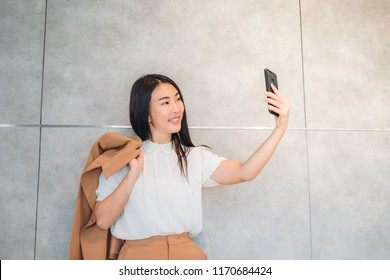 Portrait of a smiling attractive ling black hair Asian woman in brown suit taking a selfie after work.
