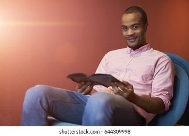 Portrait of smiling attractive male journalist thinking about ideas for new articles and publications sitting in coworking office against colorful wall with area for advertising text message