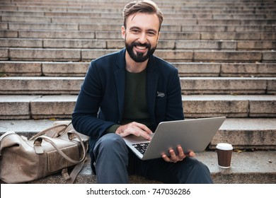 Portrait of a smiling attractive man working on laptop while sitting on a stairs outdoors
