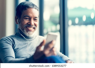 Portrait Smiling Attractive mature man retired with white stylish short beard using smartphone or listening music and sitting at coffee shop cafe.  Old man using social network internet technology