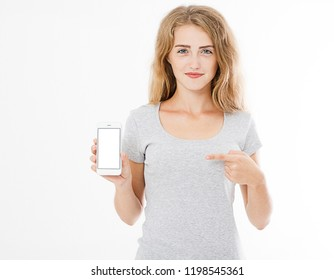 Portrait of smiling attractive, pretty, woman, girl in tshirt hold cellphone, blank screen mobilephone pointing isolated on white background, copy space.