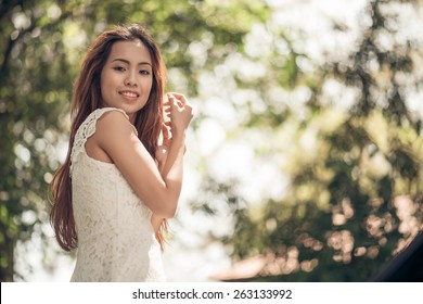 Portrait of smiling attractive Vietnamese girl in the park