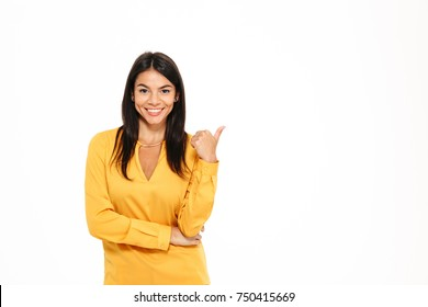 Portrait of a smiling attractive woman pointing finger away at copy space isolated over white background
