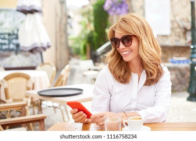 Portrait of smiling attractive woman using her mobile phone and text messaging while sitting at cafe.
