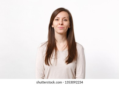 Portrait of smiling attractive young woman in light clothes standing and looking camera isolated on white wall background in studio. People sincere emotions lifestyle concept. Mock up copy space