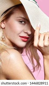 Portrait of a smiling attractive young woman in summer hat.  Female looking at camera on pink background.