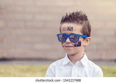 Portrait of smiling Australian boy with flag tattoo on his chick and sunglasses. Australia Day theme