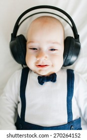 Portrait of a smiling baby boy wearing headphones and listening to classical music.