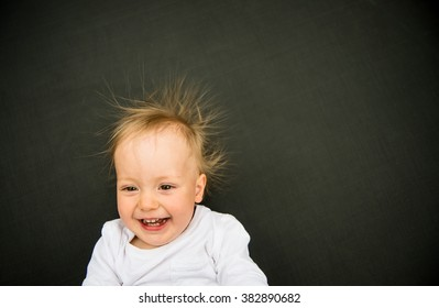 Portrait of smiling baby with standing hair from static electricity