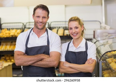 Portrait of a smiling bakers with arms crossed in bakery
