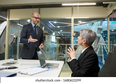 Portrait of smiling bald businessman greeting female colleague in meeting room, copy space