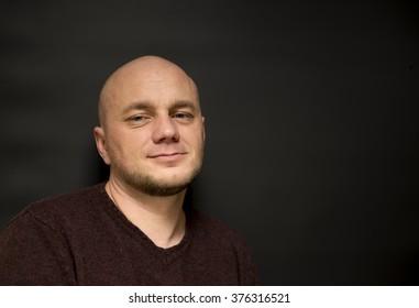 Portrait of a smiling bald man on a black background