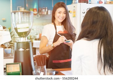 Portrait of smiling barista coffee list order from a customer with blurry background - young attractive Asian female successful in small business owner coffee shop