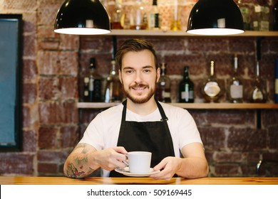 Portrait of smiling barista with facial hair with cup of coffee at the counter in bar or coffee shop. Male staff in kitchen of coffee house in blank black apron and white t-shirt holding a drink.
