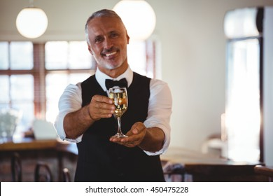 Portrait of smiling bartender standing at bar counter offering a glass of wine