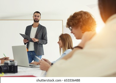 Portrait of smiling bearded coach in formal wear looking at camera while discussing architectural issues with students during workshop in university,male speaker conducts business training