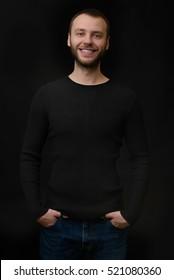 portrait of smiling bearded dude over black background