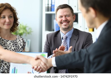 Portrait of smiling bearded man clapping hands and attractive businesswoman handshaking with biz partner. Smart colleagues reached consensus on important agreement. Blurred background