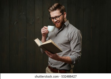 Portrait of a smiling bearded man in eyeglasses reading book and drinking cup of coffee isolated on a black wooden background