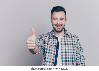 Portrait of smiling, bearded  man gesturing thumb up in checkered shirt over grey background, approving, recommend, like new product