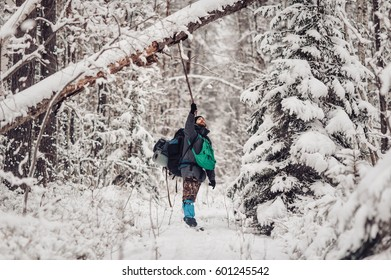 Portrait of smiling bearded man hiker, who relaxing in the winter forest. Toned image. Man with a beard tourist in a winter forest. Walks through the forest. Beats down snow