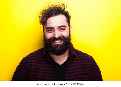 Portrait of smiling bearded man looking at the camera on yellow background