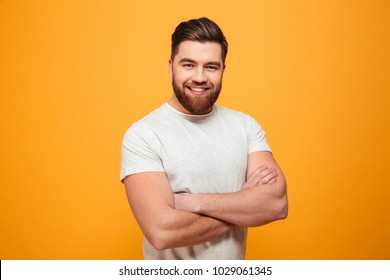 Portrait of a smiling bearded man standing with arms folded isolated over yellow background