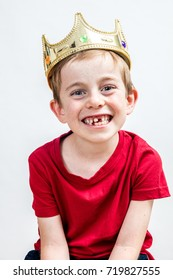 portrait of a smiling beautiful 7-year old boy with a golden crown and a missing tooth posing for a cheerful education and dental care, white background