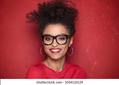 Portrait of smiling beautiful african american young woman. Girl with afro wearing eyeglasses. Red background. Studio shot.