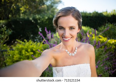 Portrait of smiling beautiful bride standing against plants in yard