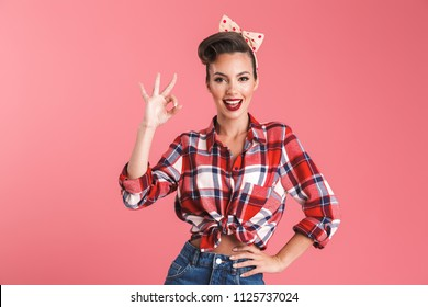 Portrait of a smiling beautiful brunette pin-up woman in headband showing ok gesture isolated over pink background