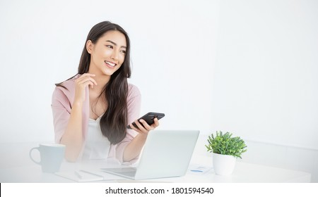 Portrait of smiling beautiful business asian woman with pink suit working in office desk using phone computer. Small business employee freelance online sme marketing e-commerce telemarketing concept