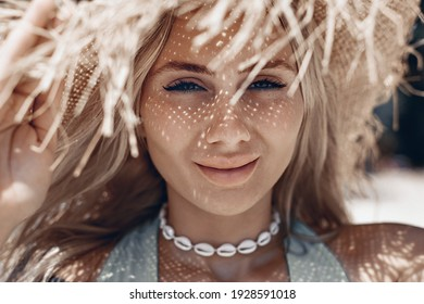 Portrait of a smiling beautiful girl with charming blue eyes and an attractive appearance in a straw panama hat.