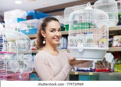 Portrait of smiling  beautiful girl choosing bird cage in petshop