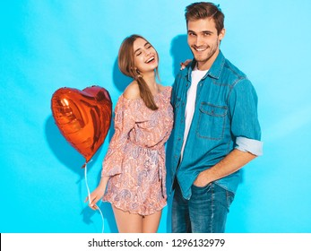 Portrait of Smiling Beautiful Girl and her Handsome Boyfriend holding  heart shaped air balloons and laughing. Happy Family. Love. Happy Valentine's Day. Posing on blue wall