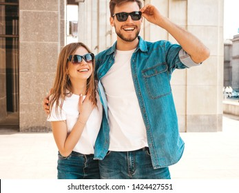 Portrait of smiling beautiful girl and her handsome boyfriend. Woman in casual summer jeans clothes. Happy cheerful family. Female having fun on the street background in sunglasses