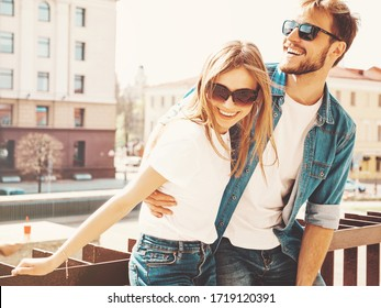 Portrait of smiling beautiful girl and her handsome boyfriend in casual summer clothes and sunglasses. Happy cheerful family having fun on the street background. Hugging