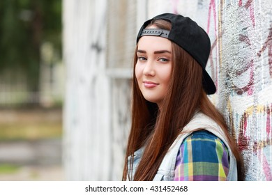 Portrait of smiling beautiful hipster girl against wall with abstract graffiti