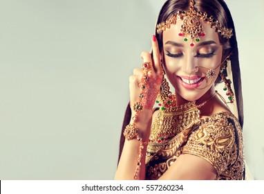 Portrait  smiling of beautiful indian girl. Young hindu woman model with golden kundan jewelry set . Traditional Indian costume lehenga choli .