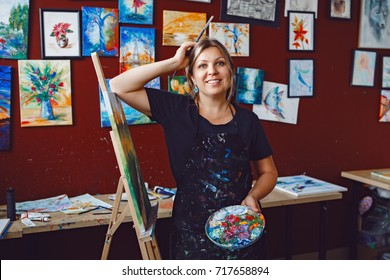 Portrait of smiling beautiful middle age white Caucasian woman artist in her art studio with paintbrush and palette. Lifestyle activity hobby concept.