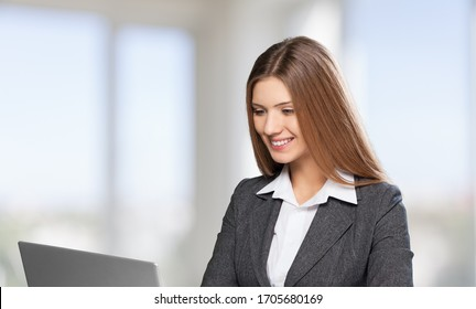 Portrait of smiling beautiful millennial businesswomanworking with laptop