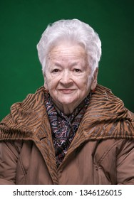 Portrait of smiling beautiful old woman on a green background