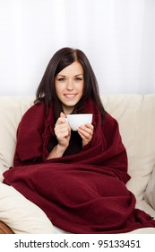 Portrait of smiling beautiful pretty young woman drinking hot coffee at home - indoors covered with blanket holding cup of tea, sitting on sofa, couch