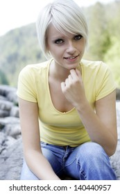 Portrait of a smiling beautiful short-haired blond woman with blue eyes, holding the chin with the hand and wearing casual clothing in an outdoors scenario